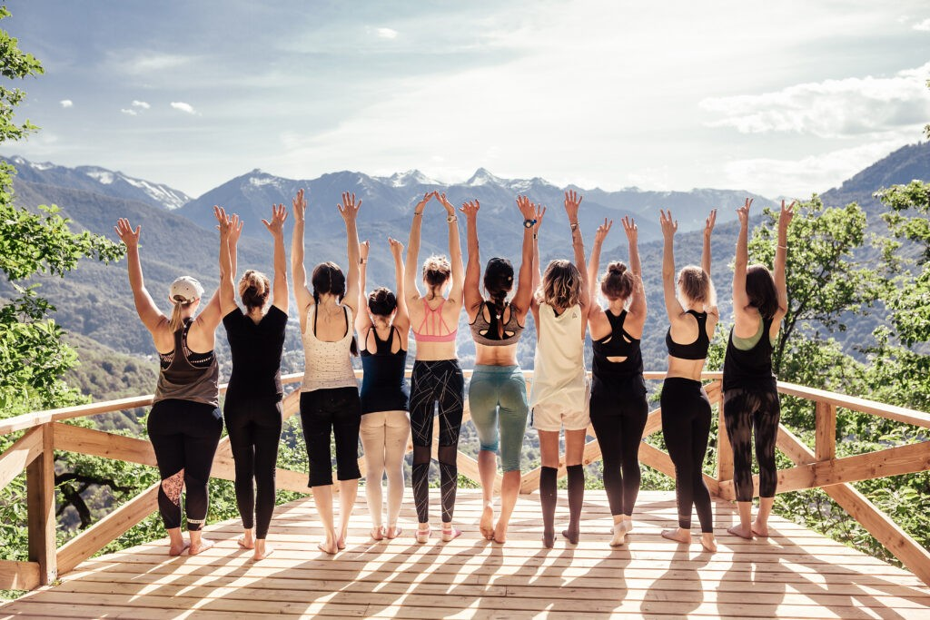 Rear view of group of joyful happy athletic young women in gymnastic clothes raise their hands up and enjoy joint activities in open air among mountains.