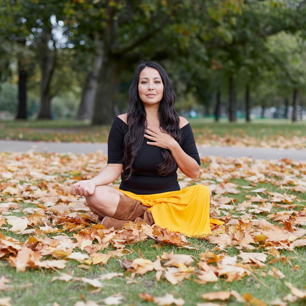 Nicky Clinch sitting cross-legged outside in a park, she is surrounded by leaves on the ground. Her left hand is on her heart, her right turned upright and on her left knee